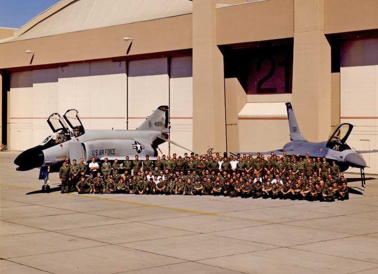 Members of the 114th Tactical Training Fighter Squadron pose for a group photo in front of an F-4 Phantom and an F-16 Falcon, both bearing the distinct Kingsley tail flash.  In 1989, the F-4 Schoolhouse converted to an F-16 training mission as the Air Force transitioned the alert mission to the F-16 Falcon.  (U.S, Air National Guard file photo)