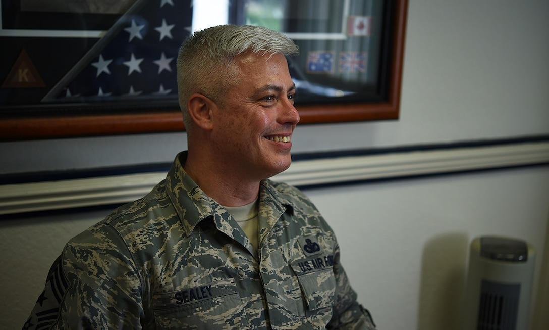 """Chief Master Sgt. Robert Sealey, 501st Combat Support Wing command chief, smiles broadly, inside his office on RAF Alconbury, United Kingdom, April 28, 2016, while recalling the """"best day"""" through his 30 year career in the U.S. Air Force. It wasn't making rank, the accolades or awards, Sealey said - it was watching his son graduate from Air Force basic military training. (U.S. Air Force photo by Tech. Sgt. Jarad A. Denton/Released)"""