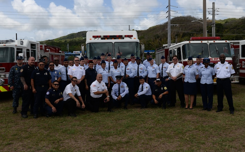 Emergency responders stand for a group photo in front of firetrucks at the emergency medical services proclamation signing event May 16, 2016, in Adelup, Guam. Four Airmen from the 36th Medical Group and 36th Civil Engineer Squadron fire and emergencies services flight received awards in multiple categories including Emergency Medical Technician of the Year and Paramedic of the Year. (U.S. Air Force photo by Airman 1st Class Jacob Skovo)