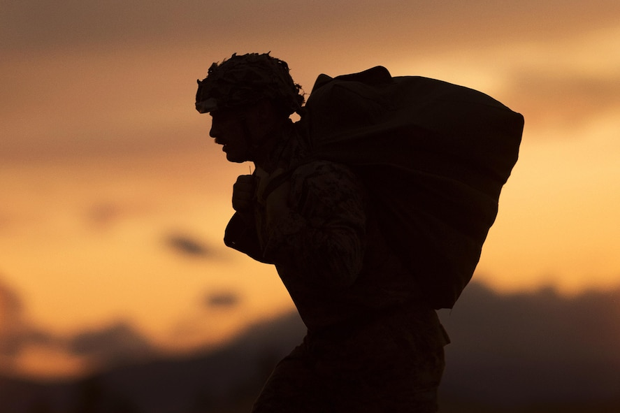 Marine Corps Cpl. Joshua Coulter carrying his parachute from the drop zone to the rally point.