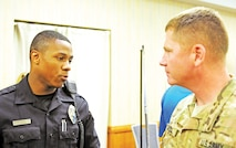 """Maj. Everett Bogle, Division Headquarters and Headquarters Battalion, 1st Infantry Division, talks with K. Robinson, patrolman, Amarillo, Texas Police Department, about upcoming academy classes and the process for application at the Hiring Heroes Career Fair April 20 at Riley's Conference Center. Representatives from 83 companies attended the career fair and met with 375 job seekers. """"We like the military background,"""" Robinson said. """"In our police department, we really recommend military guys."""""""