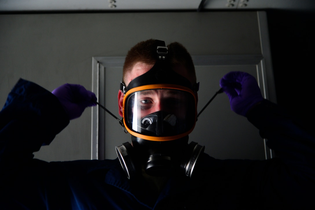 Staff Sgt. Daniel Fink, a 436th Civil Engineer Squadron Pest Management supervisor, dons a respirator before treating a C-17 Globemaster III for the Zika virus May 11, 2016, at Dover Air Force Base, Del. All U.S. aircraft are now required to be treated for Zika before flying into or through Italy. (U.S. Air Force photo/Senior Airman William Johnson)