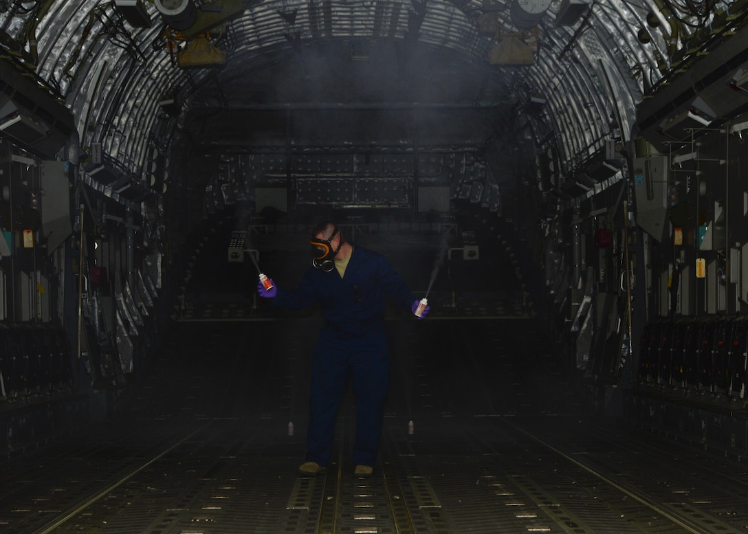 Staff Sgt. Daniel Fink, a 436th Civil Engineer Squadron Pest Management supervisor, places aerosol fog canisters of Callington 1-Shot inside of a C-17 Globemaster III to treat for mosquitos that are potentially carrying the Zika virus May 11, 2016, at Dover Air Force Base, Del. Once the aerosol cans are fully dispensed, the aircraft is sealed for 15-20 minutes so the treatment can take effect. (U.S. Air Force photo/Senior Airman William Johnson)