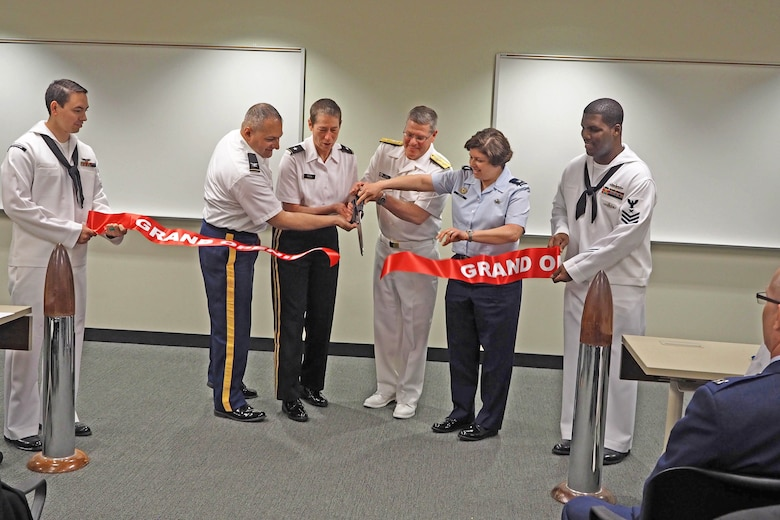 From left, Col. Aram Sarafian, Joint Reserve Intelligence Program; Brig. Gen. Christie Nixon, Military Intelligence Readiness Command; Rear Adm. Daniel MacDonnell, Naval Information Force Reserve commander and Col. Deborah Cricklin, Office of the Secretary of Defense; cut the ceremonial ribbon for the newly renovated Joint Reserve Intelligence Center at the Minneapolis-St. Paul Air Reserve Station May 13. (Air Force Photo/Paul Zadach)