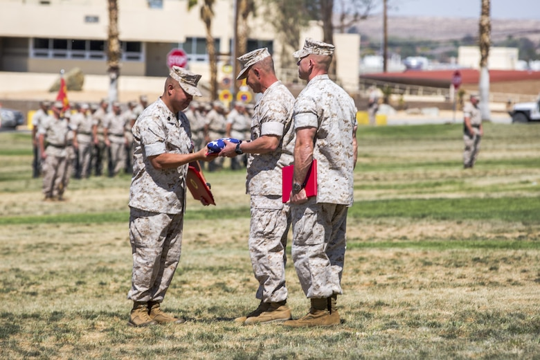 Maj. Gen. Lewis A. Craparotta, Combat Center Commanding General, presents the nation's colors to Sgt. Maj. Karl Villalino, former Combat Center Sergeant Major, during a relief and appointment ceremony at Lance Cpl. Torrey L. Gray Field May 10, 2016. During the ceremony, Villalino relinquished his post as Combat Center Sergeant Major to Sgt. Maj. Michael J. Hendges and retired after 30 years of honorable service. (Official Marine Corps photo by Lance Cpl. Levi Schultz/Released)