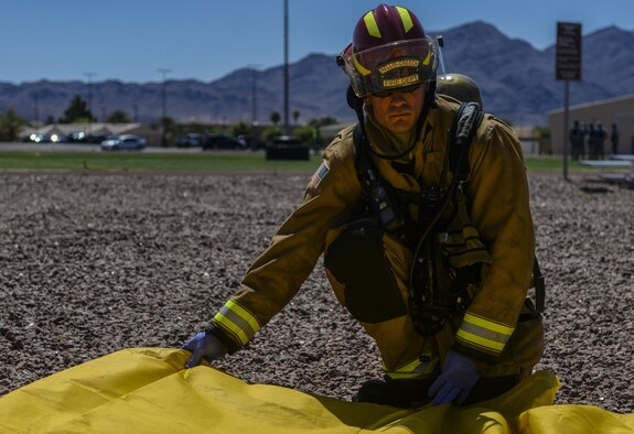 A 99th Civil Engineer Squadron Fire Protection Flight Airman spreads open a yellow triage tarp during a base exercise at Nellis Air Force Base, Nev., May 12, 2016. The simulated attacks occurred at the track at the Warrior Fitness Center during a mock squadron PT and at Hangar 220 during a mock ceremony. (U.S. Air Force photo by Airman 1st Class Kevin Tanenbaum)