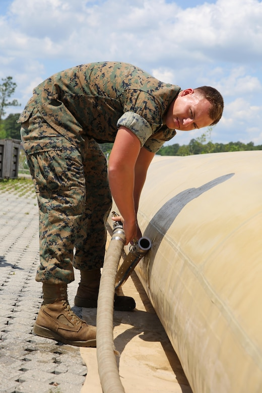 A Marine on the camp commendant's staff connects hoses to top off the water supply for shower tents during Marine Expeditionary Force Exercise 2016, at Marine Corps Air Station Cherry Point, N.C., May 11, 2016. MEFEX 16 is a command and control exercise conducted in a deployed environment designed to synchronize and bring to bear the full spectrum of II MEF's C2 capabilities in support of a Marine Air-Ground Task Force. (U.S. Marine Corps photo by Lance Cpl. Mackenzie Gibson/Released)