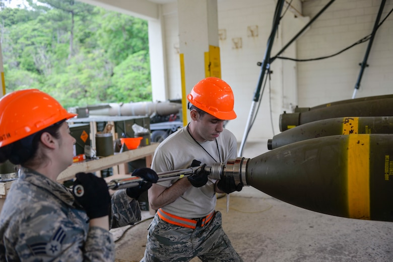 "U.S. Air Force Senior Airman Talia lamanuzzi, 366th Equipment Maintenance Squadron bomb inspector, and Airman 1st Class Jacob Israel, 18th Munitions Squadron munitions crew chief, torque the head onto a ""Big Bomb"" during a week-long Pacific Air Forces Combat Ammunition Production Exercise May 16, 2016, at Kadena Air Base, Japan. Units from Air Combat Command and Pacific Air Forces participated in the exercise to test the munitions Airmen's ability to build ammunition for wartime aircraft. (U.S. Air Force photo by Senior Airman Stephen G. Eigel/Released)"