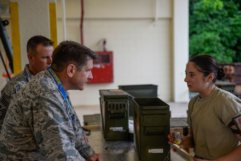 U.S. Air Force Senior Airman Talia lamanuzzi, 366th Equipment Maintenance Squadron bomb inspector, explains the bomb inspection process to Col. Christopher Amrheinn, 18th Wing vice commander, and Chief Master Sgt. Charles Hoffman, 18th Wing command chief, during a week-long Pacific Air Forces Combat Ammunition Production Exercise May 16, 2016, at Kadena Air Base, Japan. The exercise is a Pacific Air Forces exercise held annually to test the munitions Airmen's ability to build ammunition for wartime aircraft. (U.S. Air Force photo by Senior Airman Stephen G. Eigel)