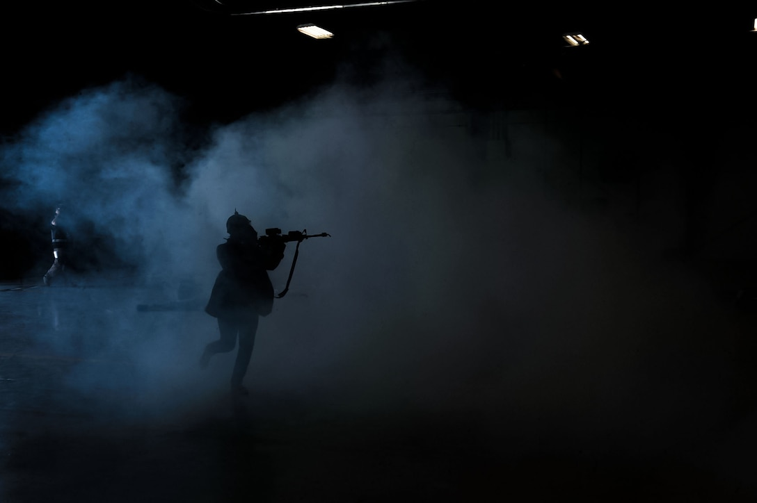 A simulated active shooter runs through building 220 on Nellis Air Force Base, Nev., during a base-wide exercise held May 12, 2016. Nellis AFB conducted a base wide exercise that involved multiple possible real-life scenarios to test the response capabilities of emergency personnel and the base. (U.S. Air Force photo by Senior Airman Rachel Loftis)