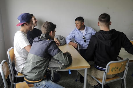 Cpl. Marcoantonio Gonzalez, a personnel administrative specialist with Special Purpose Marine Air-Ground Task Force Crisis Response-Africa engages in an English conversation with students at Instituto Professionale Alberghiero, Italy during a community relation May 11, 2016.  After nutrition classes, Marines and sailors demonstrated exercise techniques to increase the student's knowledge about physical fitness before breaking into small groups to help further develop their English skills. (U.S. Marine Corps photo by Cpl. Alexander Mitchell/released)