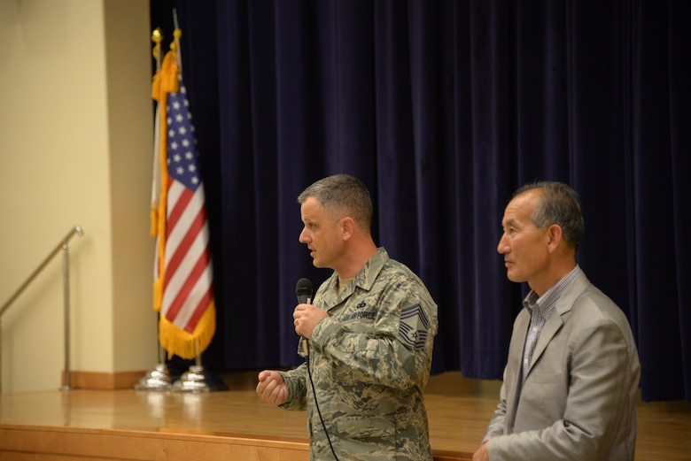 Chief Master Sgt. James Segebarth, 51st Mission Support Group superintendent, gives encouraging advice to the participants of the Osan Good Neighbor English Camp while Yi, Chong Kun, 51st Fighter Wing public affairs community outreach advisor, translates during a ceremony May 18, 2016, in the American Middle School at Osan Air Base, Republic of Korea. The ceremony culminated a three-day English camp where Korean students from the local area had the opportunity to live with a family from Osan AB and learn about American culture. The English Camp program started in 2005 and has helped strengthen the community relationship between local Koreans and American service members and their families. (U.S. Air Force photo by Tech. Sgt. Travis Edwards/Released)