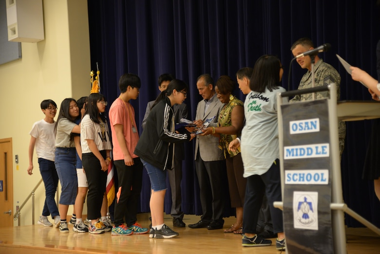 Osan American Middle School and Korean students receive certificates commemorating the completion of the Osan Good Neighbor English Camp during a ceremony May 18, 2016, in the OAMS at Osan Air Base, Republic of Korea. The English Camp paired Korean students with OMS families for three days to learn about American culture, shadow American students during class, and featured a tour of Osan AB for the students and their families. The English Camp program started in 2005 and has helped strengthen the community relationship between local Koreans and American service members and their families. (U.S. Air Force photo by Tech. Sgt. Travis Edwards/Released)