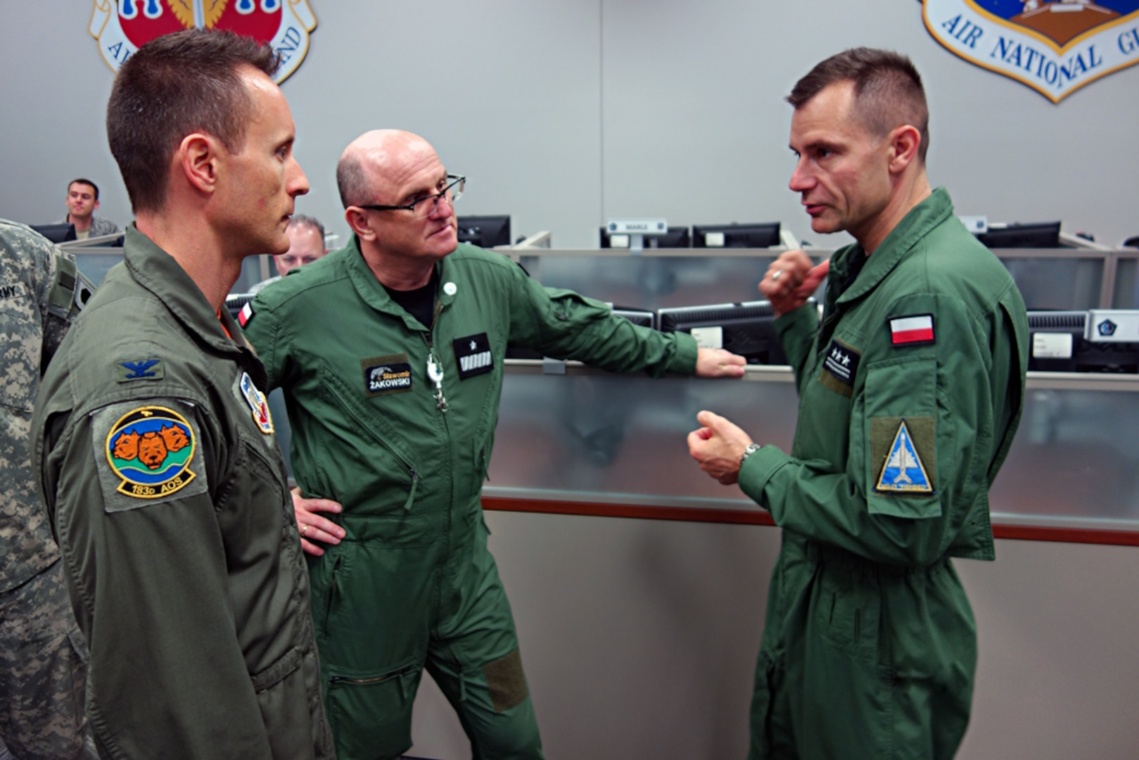 Dan McSeveney, left, commander of the 183d Combat Operations Squadron,discusses air operations with Brig. Gen. Slawomir Zakowski, center, and Col. Robert Weissgerber, right, from the Air Operations Center-Air Component Command, Warsaw, Poland, during a simulated battle exercise as part of an information and training exchange visit May 12 - 16, 2016, in Springfield, Ill.