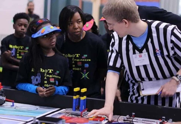 "RICHMOND, Va. – Naval Surface Warfare Center Dahlgren Division (NSWCDD) engineer Serita Seright, 2nd from right, and a student, listen to a judge explain the FIRST LEGO League (FLL) competition rules and point system at Maggie Walker Governor High School in November 2015. Seright – who mentors a FLL student team called the ""Robot Engineers"" – was honored by the National Society of Black Engineers (NSBE) as the Region II ""Professionals Member of the Year"" for leadership impacting its mission in Virginia, NSWCDD announced, May 16. ""I'm humbled to be recognized for personifying the NSBE mission – to increase the number of culturally responsible black engineers who excel academically, succeed professionally, and positively impact the community,"" said Seright, in response to the news. The  award recognizes individuals who make outstanding contributions to NSBE, especially their chapter and region, in the areas of leadership, excellence, service, and advancement of its programs and mission."