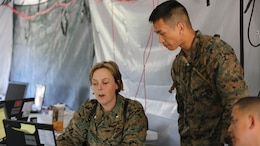 Lt. Col. Regina Gustavsson and Sgt. Peter Apiag discuss reporting requirements for their section for a simulated mishap during II Marine Expeditionary Force Exercise 16 at Marine Corps Air Station Cherry Point, N.C., May 11, 2016. MEFEX 16 is a command and control exercise conducted in a deployed environment designed to synchronize and bring to bear the full spectrum of II Marine Expeditionary Force's C2 capabilities in support of a Marine Air-Ground Task Force.