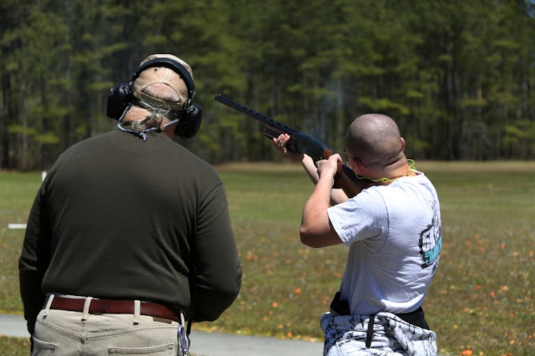 Kevin Driscoll (left) supervises Cpl. Joshua Wade during a trap and skeet range at Marine Corps Air Station Cherry Point, N.C., April 14, 2016. Twenty Marines with 2nd Low Altitude Air Defense Battalion's Firearms Mentorship Program utilized their marksmanship skills during the range as part of their firearms safety classes. The mentorship program promotes safe private gun ownership, builds confidence in marksmanship skills and increases Marines combat readiness by familiarizing them with other weapons. Driscoll is the range safety officer with the MCAS Cherry Point Skeet Club and Wade is a ground radio operator with the battalion. (U.S. Marine Corps photo by Cpl. N.W. Huertas/ Released)