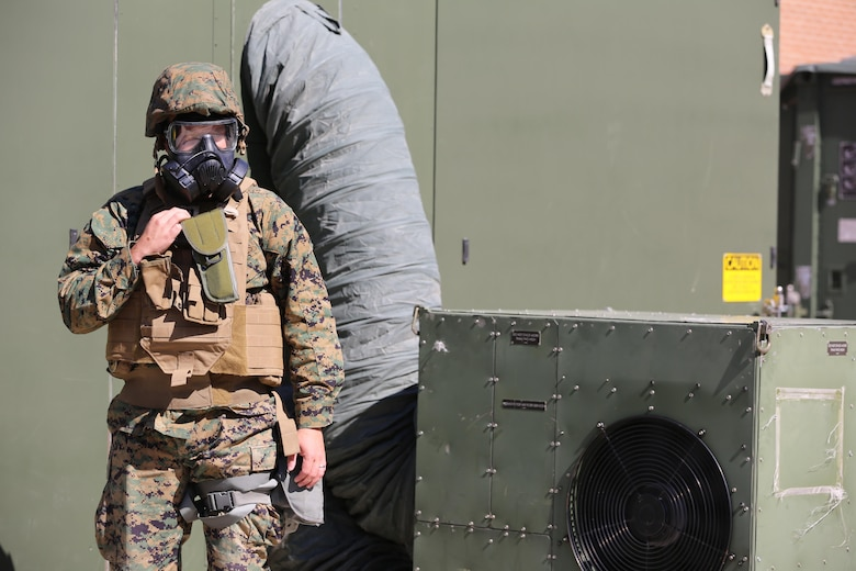 A Marine ensures others don their gas masks during a chemical, biological, radiological and nuclear defense drill as part of 2nd Marine Aircraft Wing's portion of the Marine Expeditionary Force Exercise 2016 at Marine Corps Air Station Cherry Point, N.C., May 15, 2016. The purpose of the drill was to ensure that the Marines knew how to react quickly and use their equipment properly. MEFEX 16 is designed to synchronize and bring to bear the full spectrum of II MEF's command and control capabilities in support of the Marine Air-Ground Task Force. (U.S. Marine Corps photo by Staff Sgt. Rebekka S. Heite/Released)
