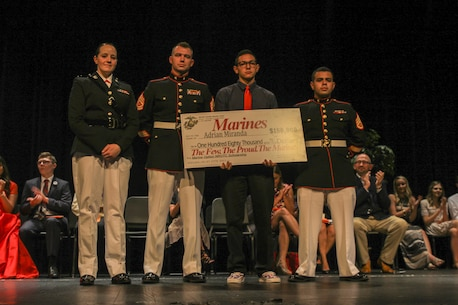 Captain Jennifer Mozzetta, executive officer for Recruiting Station Orlando, Gunnery Sgt. Gregory Hauk, station commander for Recruiting Substation Orlando, and Staff Sgt. Magno Choez, a recruiter for RSS Orlando, award Adrian Miranda, a senior at Boone High School, the NROTC Scholarship during an awards ceremony May 18, 2016, at Boone High School.