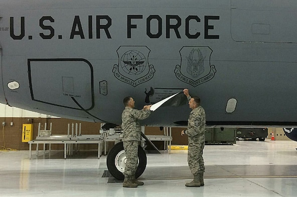 Lt. Col. Duane Richardson, the 22nd Aircraft Maintenance Squadron commander, left, and Chief Master Sgt. Joseph Thomas, the 22nd AMXS superintendent, reveal the dedicated crew chief box on a KC-135 Stratotanker May 2, 2016, at McConnell Air Force Base, Kan. The 22nd AMXS and the 931st Aircraft Maintenance Squadron held a DCC induction ceremony where 58 DCCs and assistant DCCs were assigned to 25 KC-135 Stratotankers. (Courtesy photo)