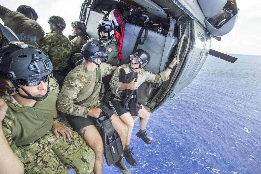 U.S. and Australian sailors prepare to fast-rope from an MH-60S Seahawk helicopter.