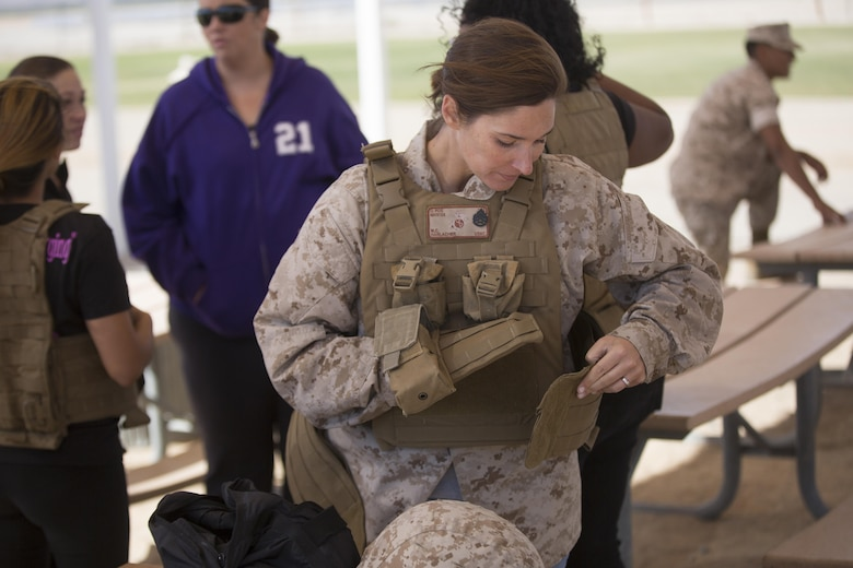 Jennifer Harlacher, wife of Staff Sgt. Matthew Harlacher, motor transportation chief, Marine Wing Support Squadron 374, adjusts her husband's plate carrier at Del Valle Field during the squadron's Jane Wayne Day April 29, 2016. (Official Marine Corps photo by Cpl. Julio McGraw/Released)