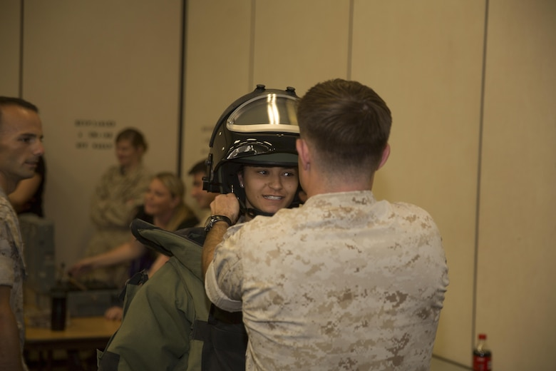Gabriella Martin, wife of Lance Cpl. Jacob Martin, aircraft rescue and firefighting specialist, Marine Wing Support Squadron 374, tries on the bomb disposal suit, during the squadrons Jane Wayne Day, at Bldg. 1707 April 29, 2016. (Official Marine Corps photo by Cpl. Julio McGraw/Released)