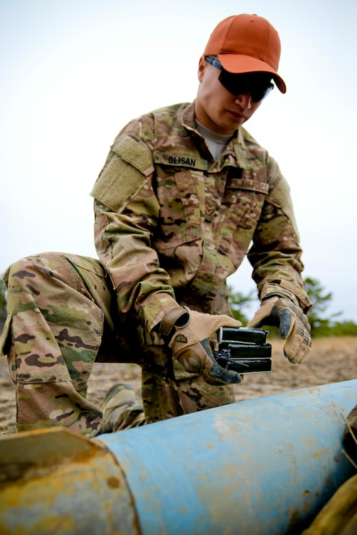U.S. Air Force Airman 1st Class Michael Glisan, Explosives Ordnance Disposal Technician with the 87th Civil Engineering Squadron, Joint Base McGuire-Dix-Lakehurst, N.J., prepares to triple stack C-4 explosives on used practice bombs to render them safe for recycling at Warren Grove Range in Ocean County, N.J. on April 29, 2016. EOD members, civil engineers and range crew from the 177th Fighter Wing of the New Jersey Air National Guard worked together during the annual EOD Week At The Range to perform range clean-up and target painting, as well as target set-up in the simulated village. (U.S. Air National Guard photo by Master Sgt. Andrew J. Moseley/Released)