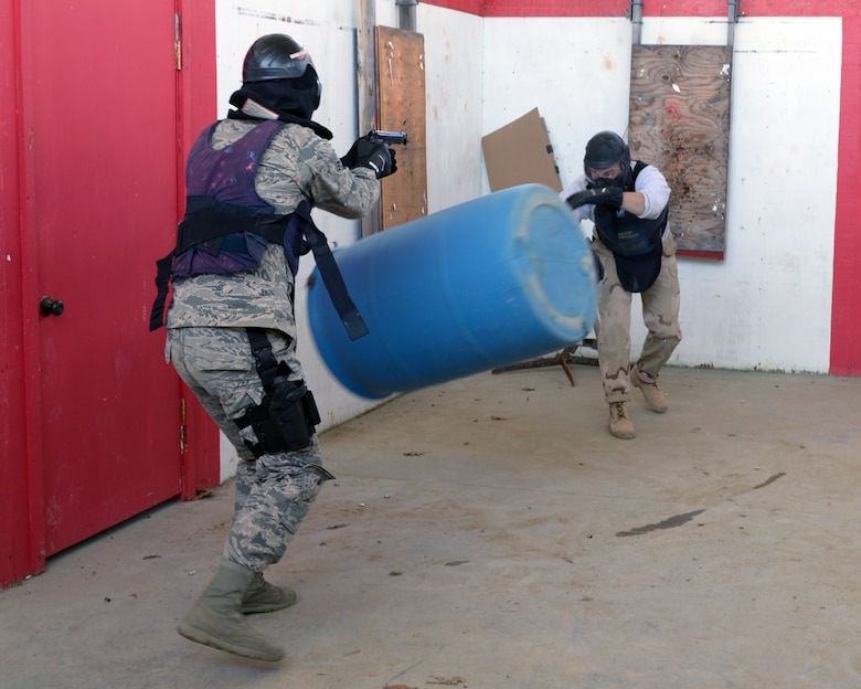 U.S. Air Force Tech. Sgt. Thomas J. Moore, 157th Security Forces Squadron flight chief, throws a barrel at Senior Airman Jonathan M. Oconnell, 157 SFS member, during a use of force training scenario at Sig Sauer Academy, Epping, N.H. May 14, 2016. The personal protective equipment they are wearing provides them protection from the non-lethal training ammunition tipped with colored dye which they are using.  (U.S. Air National Guard photo by Airman 1st Class Ashlyn J. Correia)
