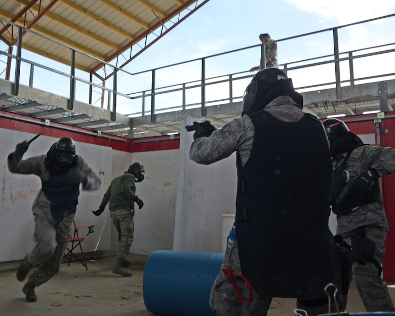 U.S. Air Force Staff Sgt. Michael P. Johnson, 157th Security Forces Squadron NCO in charge of Combat Arms, left, attempts to attack Airmen from the 157 SFS during a use of force training scenario at Sig Sauer Academy, Epping, N.H. May 14, 2016. The personal protective equipment they are wearing provides them protection from the non-lethal training ammunition tipped with colored dye which they are using. (U.S. Air National Guard photo by Airman 1st Class Ashlyn J. Correia)