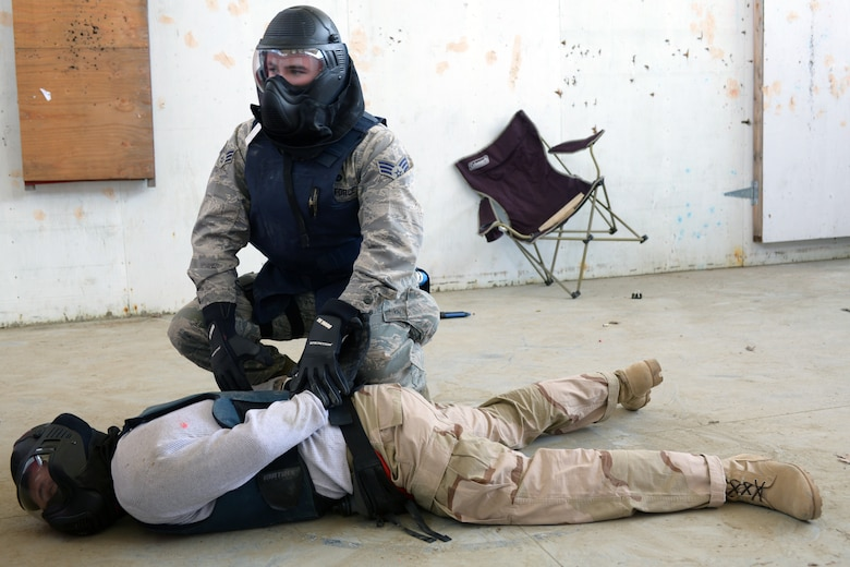 U.S. Air Force Senior Airman Brandan J. Abel, 157th Security Forces Squadron member, secures Tech. Sgt. Thomas J. Moore, 157 SFS flight chief, during a use of force training scenario at Sig Sauer Academy, Epping, N.H. May 14, 2016. The personal protective equipment they are wearing provides them protection from the non-lethal training ammunition tipped with colored dye which they are using.  (U.S. Air National Guard photo by Airman 1st Class Ashlyn J. Correia)
