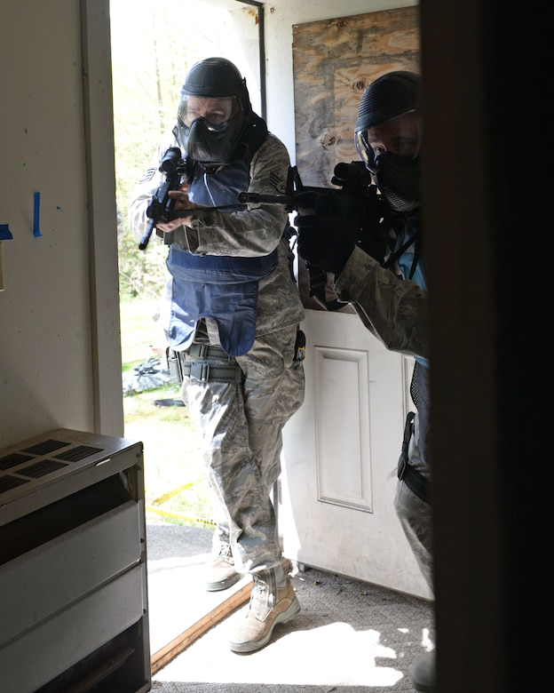 U.S. Air Force Staff Sgt. Michael P. Johnson, 157th Security Forces Squadron NCO in charge of Combat Arms, left, and Tech. Sgt. Philip J. Soares, 157 SFS craftsman move through a doorway during an active shooter training scenario at Sig Sauer Academy, Epping, N.H. May 14, 2016.  The personal protective equipment they are wearing provides them protection from the non-lethal training ammunition tipped with colored dye which they are using. (U.S. Air National Guard photo by Airman 1st Class Ashlyn J. Correia)