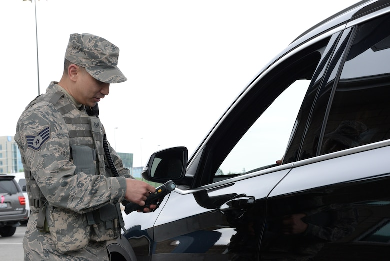 Staff Sgt. Michael G. Fong with the 129th Rescue Wing checks a members identification card during gate guard duty, Moffett Federal Airfield, Calif., April 2, 2016. Fong works as an Augmentee for the 129th Security Forces Squadron. (U.S. Air National Guard photo by Senior Airman Zachiah Roberson/Released)
