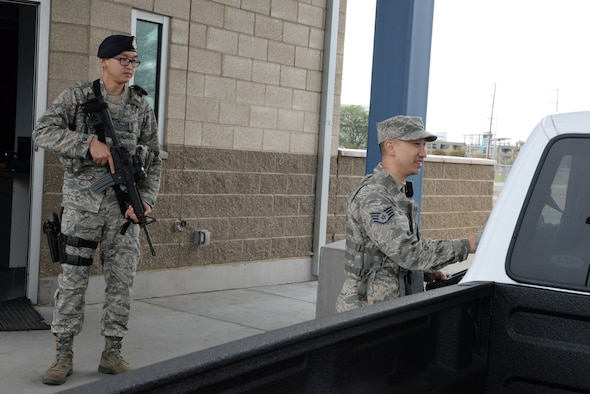 Staff Sgt. Michael G. Fong with the 129th Rescue Wing (right) checks a members identification card during gate guard duty, Moffett Federal Airfield, Calif., April 2, 2016. Fong works as an Augmentee for the 129th Security Forces Squadron. (U.S. Air National Guard photo by Senior Airman Zachiah Roberson/Released)