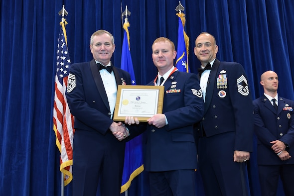 MCGHEE TYSON AIR NATIONAL GUARD BASE, Tenn. - Staff Sgt. Jason Savary, 193rd Special Operations Maintenance Readiness Squadron, center, takes his diploma here May 18, 2016, as a distinguished graduate of the Airman leadership school, as well as recipient of the John L. Levitow award, class 16-5, during the graduation banquet at the Chief Master Sgt. Paul H. Lankford Enlisted Professional Military Education Center. He is joined on stage by 12th Chief Master Sgt. of the Air Force Eric W. Benken, retired, and Chief Master Sgt. Edward L. Walden Sr., right, Lankford Center commandant. (U.S. Air National Guard photo by Master Sgt. Mike R. Smith/Released)