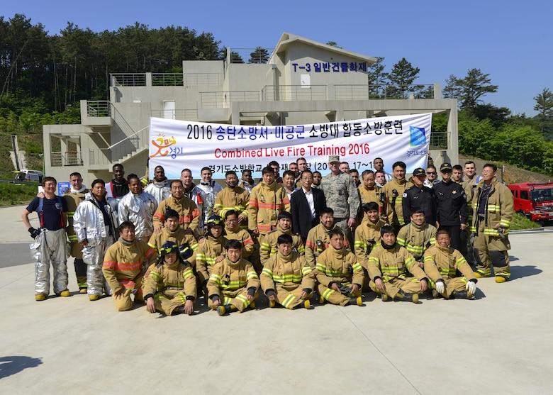 Firefighters from the 51st Civil Engineer Squadron fire and emergency services flight pose with members of the Songtan fire department at the Kyonggi-do Fire Academy, Republic of Korea, May 18, 2016. The firefighters prepared for a live fire training exercise at the fire academy. (U.S. Air Force photo by Senior Airman Victor J. Caputo/Released)