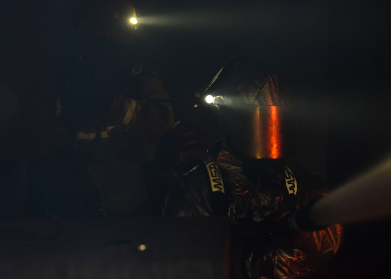 Firefighters from the 51st Civil Engineer Squadron fire and emergency services flight douse a fire during structural live fire training at the Kyonggi-do Fire Academy, Republic of Korea, May 18, 2016. Small teams of firefighters tested their ability to extinguish structural fires inside high-heat, low-visibility situations during the training. (U.S. Air Force photo by Senior Airman Victor J. Caputo/Released)