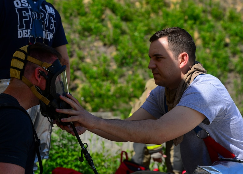 Staff Sgt. Michael White, 51st Civil Engineer Squadron fire and emergency services flight fire communications NCO in charge, helps adjust his wingman's oxygen mask at the Kyonggi-do Fire Academy, Republic of Korea, May 18, 2016. The firefighters were preparing for live fire training which required them to wear all protective and heat resistant gear. (U.S. Air Force photo by Senior Airman Victor J. Caputo)