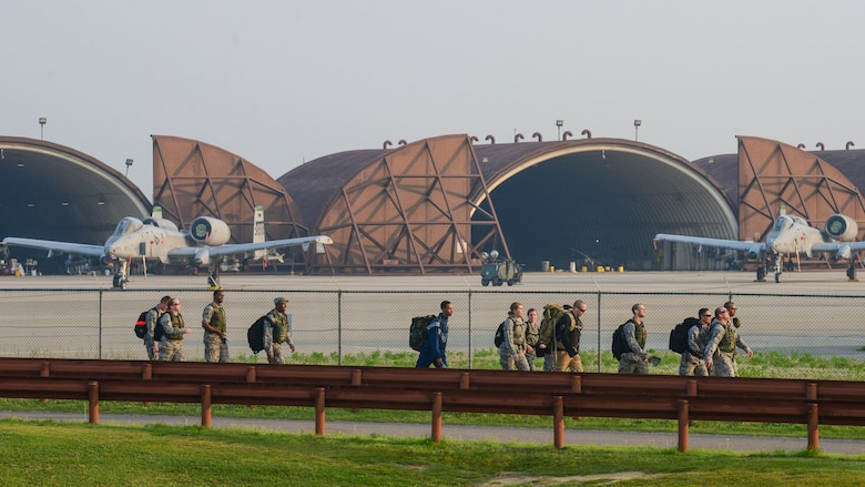 Members of Team Osan march past the flightline during a commemorative ruck march at Osan Air Base, Republic of Korea, May 20, 2016. The march, which was a part of Asian-American and Pacific Islander Heritage Month, was hosted by the 607th Air Support Operations Group in commemoration of the Bataan Death March. Approximately 70,000 American and Filipino troops were forcibly marched 60 miles by the Imperial Japanese Army after being defeated in the three-month Battle of Bataan. Thousands of the troops died before reaching their final destination at Camp O'Donnell, a Japanese prisoner of war camp. (U.S. Air Force photo by Senior Airman Victor J. Caputo/Released)