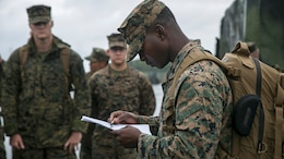 Master Sgt. Leroy A. Forbes reads off names for accountability for Task Force Koa Moana at Tengan Pier, Okinawa, Japan on May 18, 2016. The task force is responsible for conducting a series of bilateral, multi-national exercises involving a company-sized element of Marines and Sailors from different units within III Marine Expeditionary Force. They will be traveling to countries in the Asia-Pacific region aboard the USNS Sacagawea, a Marine Prepositioning Force ship. The ship is normally a mobile warehouse for Marines' supplies; however, during this exercise, it will serve to transport personnel to multiple nations, where they will conduct basic military training and cultural exchange to increase relations and interoperability between participating nations. Forbes, from Hartford, Conn., is a combat engineer with 9th Engineer Support Battalion, 3rd Marine Logistics Group, III Marine Expeditionary Force, and is the task force's senior enlisted in charge for the series of exercises.