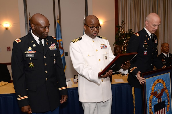 Navy Capt. Scott Giles (center), executive officer for the DLA Joint Reserve Force, presents a plaque to Army Col. Ralph Roper (left), outgoing DLA Joint Reserve Force Army Reserve Element Commander, during a May 14 dining out at Joint Base Andrews, Maryland. At right is Army Lt. Col. Bryan Brokate.