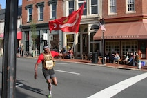 Joshua Howze, 22, of Washington, D.C., rounds the corner of William Street in downtown Fredericksburg carrying the Marine Corps flag during the Historic Half marathon May 15.