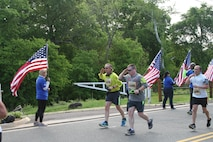 Runners salute the American flag as they pass along the Wear Blue Run to Remember Mile honoring Marines killed in action, a new feature of the Marine Corps Historic Half.