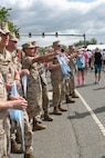 Marine Corps lieutenants hold medals at the ready as they cheer on the runners at the finish line.