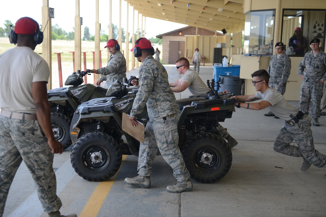 Airmen with the 9th Security Forces Squadron push ATV's during a shooting competition May 18, 2016, at Beale Air Force Base, California. Multiple two-man teams from various military and civilian law enforcement agencies participated during the competition. (U.S. Air Force photo/ Senior Airman Bobby Cummings)
