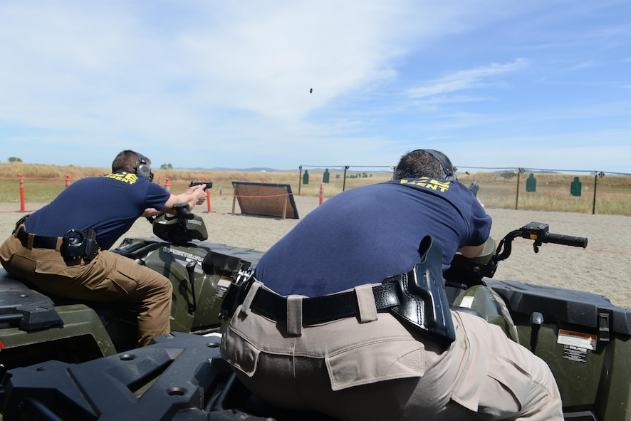 Sean Gatton (right), Air Force Office of Special Investigations special agent and David Shaver, AFOSI special agent, fire their pistols while mounted on ATV's during a shooting competition May 18, 2016, at Beale Air Force Base, California. Multiple two-man teams from various military and civilian law enforcement agencies participated during the competition. (U.S. Air Force photo/ Senior Airman Bobby Cummings)