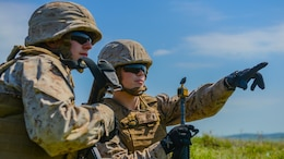 Second Lt. Virginia Brodie points out an enemy position to 2nd Lt. Katherine Boy at the Field Artillery Basic Officers Leadership Course at Fort Sill, Oklahoma, May 12, 2016. Brodie and Boy are the first two female Marine artillery officers to complete the course.