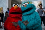 Sesame Street's Elmo and Rosita take time out for a photo op while helping to pack USO bags for deployed service members on Capitol Hill. DoD photo by Marine Staff Sgt. Drew Tech