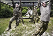 Airmen on Monster Mash Team 4 complete a monkey-bar obstacle  at Hurlburt Field, Fla., May 12, 2016. Monster Mash is a training tradition in which special operators complete timed scenarios on an obstacle course. Air Force photo by Senior Airman Ryan Conroy