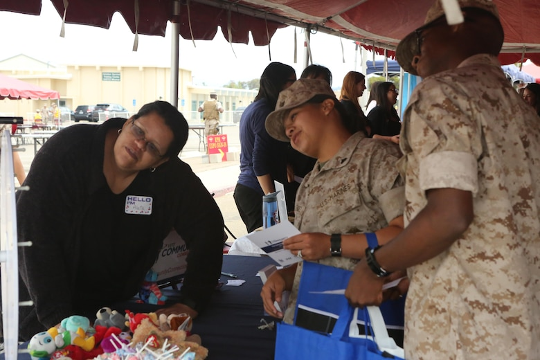 Service members play a game at a booth during the Relationships, Marriage and Parenting Exposition aboard Marine Corps Air Station Miramar, Calif., May 11. The expo provided Marines, Sailors and families of 3rd Marine Aircraft Wing with resources to strengthen relationships and families.  (U.S. Marine Corps photo by Pfc. Liah Kitchen/Released)
